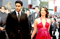 Aishwarya in her beautiful fresh hot pink gown holding hands with her husband walking down the red carpet.PNG